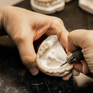using sanding tool to perfect denture set